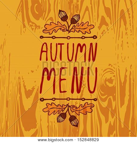 Hand-sketched typographic element with acorns and text on wooden background. Autumn menu