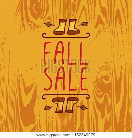 Hand-sketched typographic element with rubber boots, leaves and text on wooden background. Fall sale