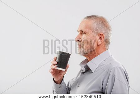 side view of an aged businessman drinking tea from a paper cup with copy space