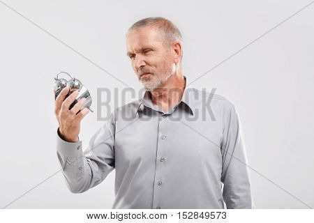 time is running, old cheerful man looking at the vintage clock in his hands against a gray background