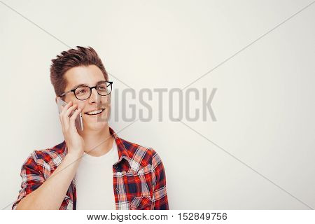 Portrait of attractive young student in casual red shirt talking on smartphone