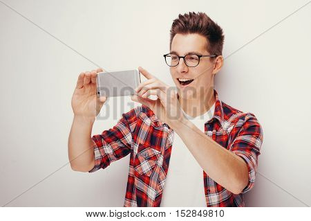 Youth and technology. Studio portrait of handsome young man in glasses using smart phone. Isolated