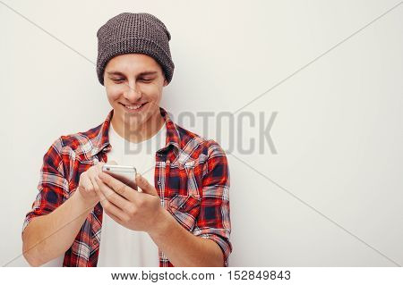 Youth and technology. Studio portrait of handsome young man in hat using smart phone. Isolated