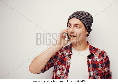 Portrait of attractive young student in casual red shirt and grey hat talking on smartphone