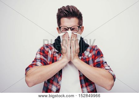 Attractive young man in red shirt and glasses got a cold. All isolated on white background.