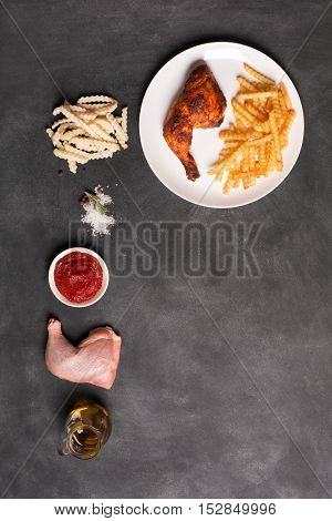 Fried Chicken leg and french fries with sauce on a black chalkboard. Top view, verticlal shot