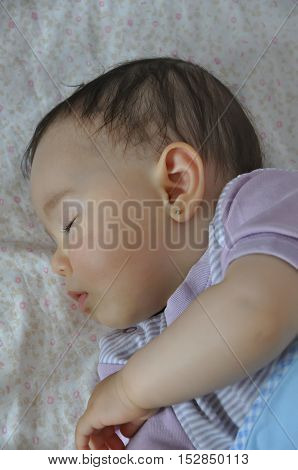 Tired baby girl sleeping. Selective focus. Ambient light.