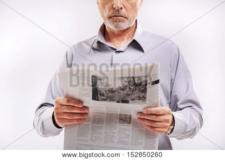 mature guy holding a newspaper in front of a camera on gray background