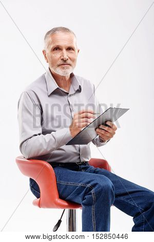 mature male holding clipboard while sitting in a studio, isolated on gray