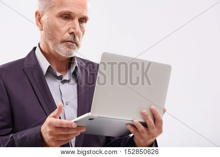 handsome aged businessman working with laptop in the studio with copy space