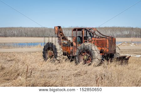 horizontal image of an orange antique heavy duty loader with a winch in the back  and big chains around the wheel and a blade in the front.