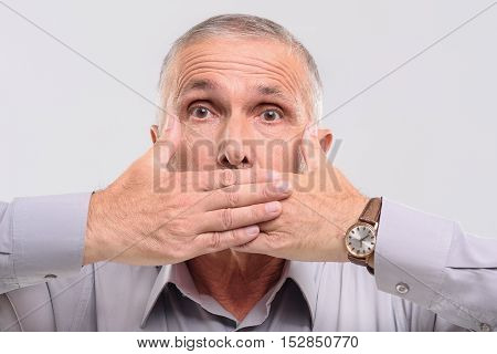 keep quiet, elderly male covering his mouth with hands