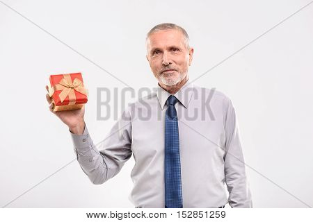 look what I have for you, smiling pensioner holding a gift box, isolated on grey