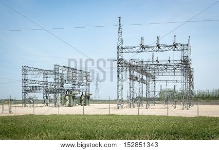horizontal image of a large electric station structure sitting under a clear blue sky in the summer time.