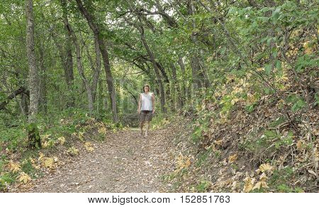 horizontal image of a smiling woman taking a leisure walk on a walking trail deep in the woods on a wide hiking trail enjoying quiet time