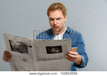 what a terrible news, shocked male standing with newspaper indoors