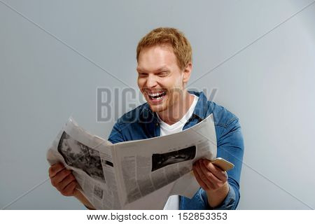 excited man holding newspaper and smartphone and laughing, isolated on gray