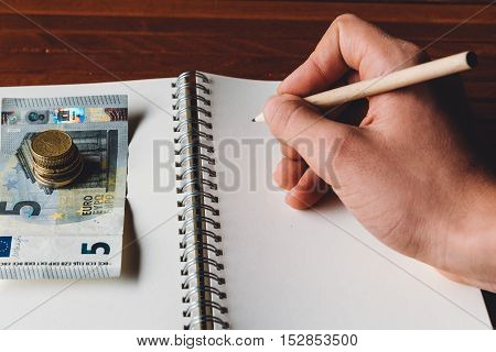 Hand with pencil on blank notebook with euro money. Focus on finger