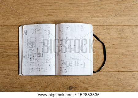Architect notebook with drawings and sketches on wooden table