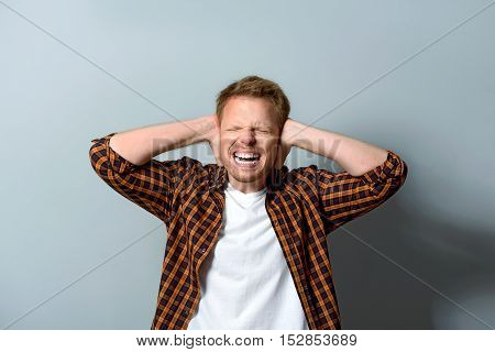 man trying to ignore the loud noise and keeping his ears shut, tinnitus concept
