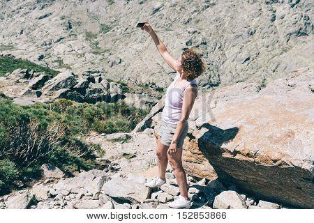 Woman hiker taking selfie photo with cellphone on mountain peak