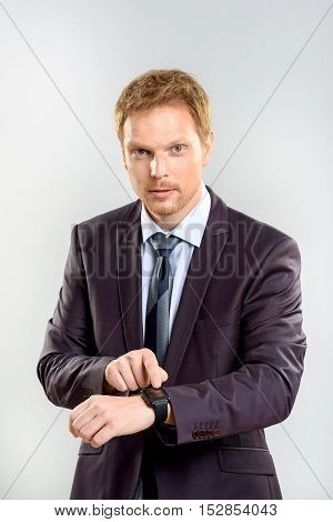 time is money, confident young man in a costume pointing his watch and looking at camera while standing against grey background