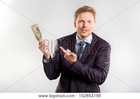 do you want some money, successful guy holding money bill and pointing at it, isolated
