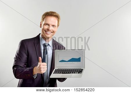 charts are perfect, happy manager holding laptop with very positive graphs, isolated with copy space