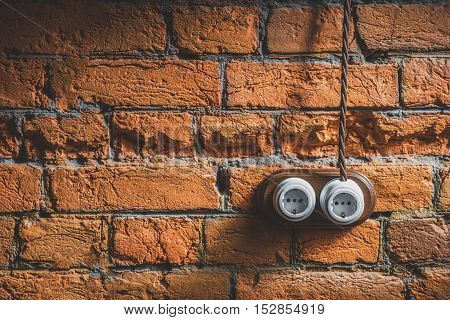 electric sockets installation on brick wall at the old house with copy space