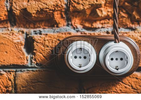 pair of unplugged electrical outlets against brick wall, close up