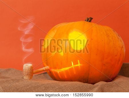 Beautiful Pumpkin on Halloween with a pipe on an orange background
