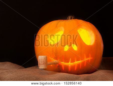 Beautiful Pumpkin on Halloween with a pipe on an black background