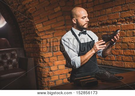 bald bearded businessman looking at shoe in his hands