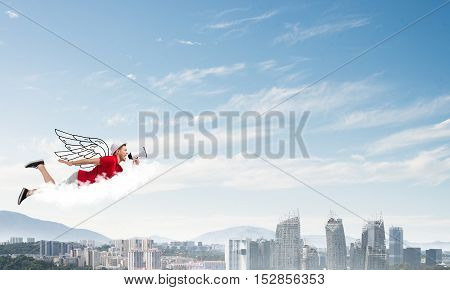 Young cheerful man with megaphone flying high above city