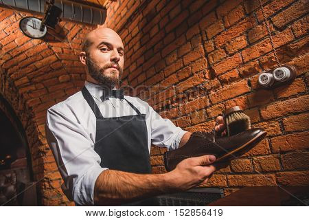 low angle view of a guy brushing brogues indoors and looking into a camera