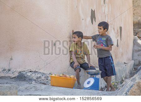 Wakan village Oman October 15th 2016: omani boys selling pomegranate fuits