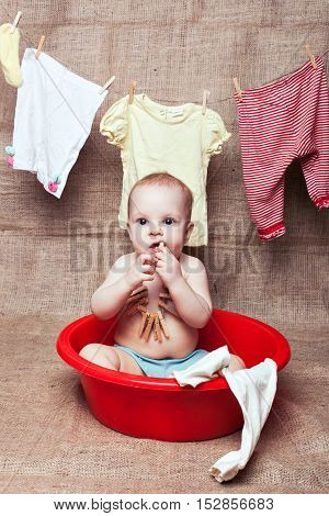 Baby girl sitting in a basin. She has a rope around his neck with wooden clothespins
