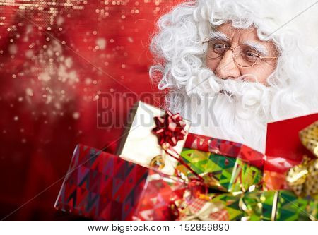 Photo of happy Santa Claus outdoors in snowfall carrying gifts to children