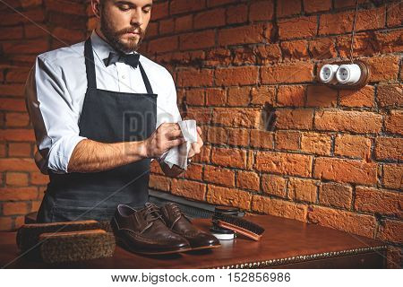 calm man wiping hands after shoe shining in the building