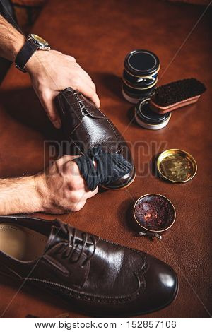 hands of a guy waxing surface of leather brogues