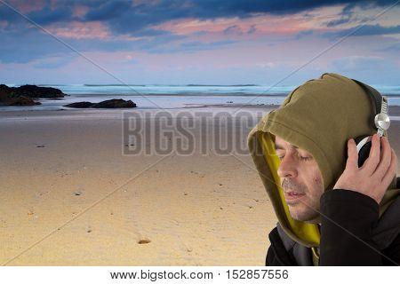 Man in hoodie listening to music on headphones