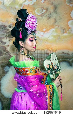 Chinese Beautiful Girl In Traditional Chinese Dress With Fan In A Half-turn