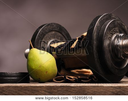 Dumbbell with gloves and a fresh green pear health concept with fresh food and sports