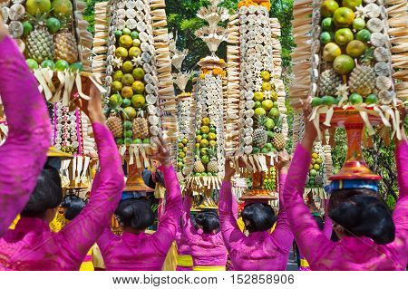 Procession of beautiful Balinese women in traditional costumes - sarong carry offering on heads for Hindu ceremony. Arts festival culture of Bali island and Indonesia people. Asian travel background
