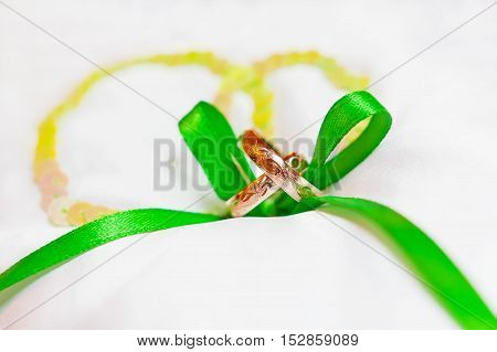 Golden wedding rings with ornament on silk background with green ribbon. Symbol of love and marriage.
