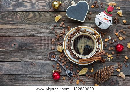 Rustic wooden background with cup of coffee and New Year decorations. Heart shaped chalkboard. Christmas beverage with ginger and anise. Top view place for text.