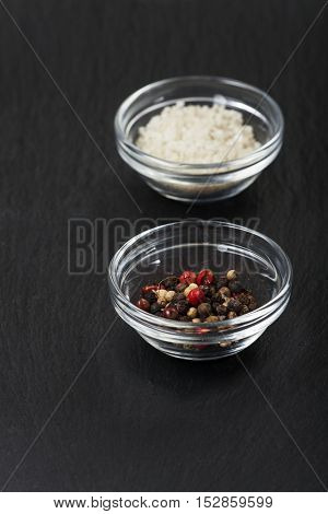 salt and pepper in glass bowls on slate