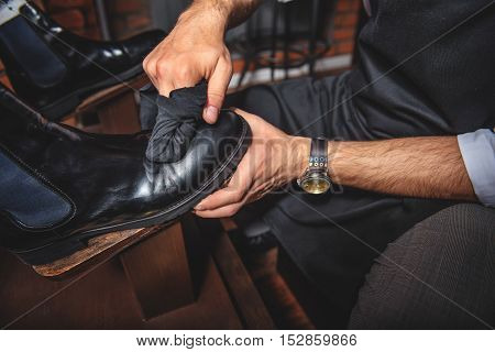man wiping black brogues with a rag while on wooden shoe platform
