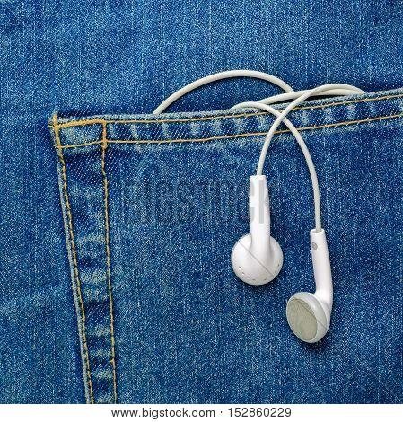 White earphones hanging off a jeans pocket. Modern Earphones.