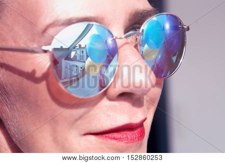 closeup of woman with glasses with reflection of colorful balloons